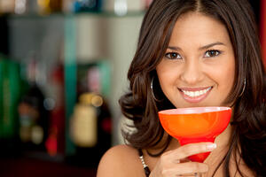 Beautiful woman portrait with a glass drinking a cocktail at a bar