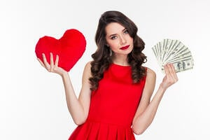 Portrait of a beautiful woman in red dress choosing between love or money isolated on a white background